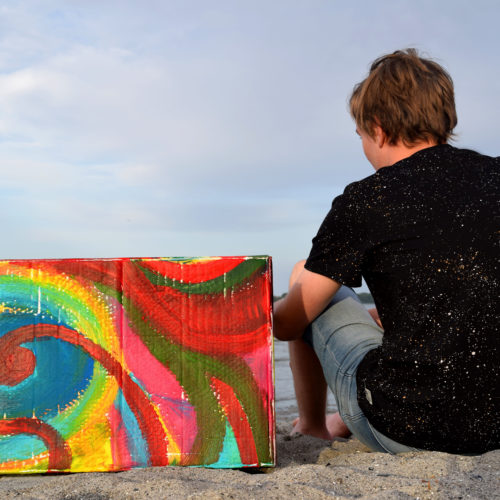 Junge mit Karton am Strand 1